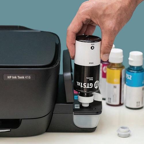 Mão abastecendo tanque de tinta da InkTank com garrafa refil preta